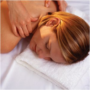 A female-presenting person laying down, getting a professional massage.