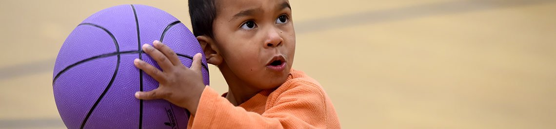 Small child holding a purple basketball, the look of determination on their face.