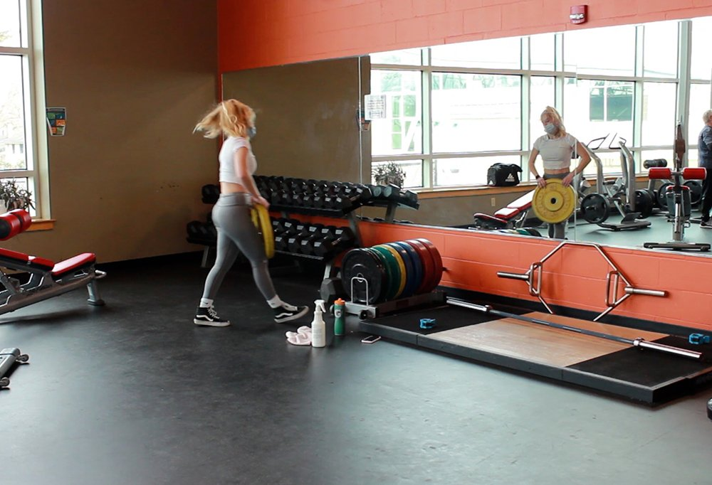 A female-presenting member using the weight room.
