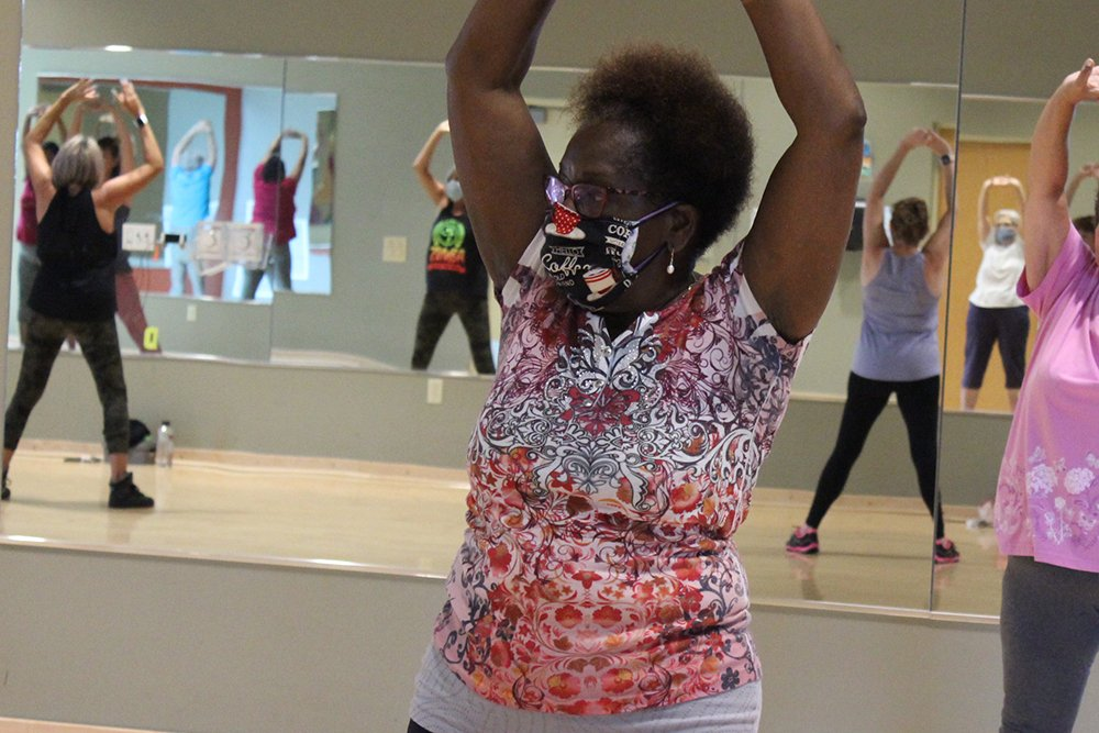 A female-presenting, senior member in a Zumba group fitness class.