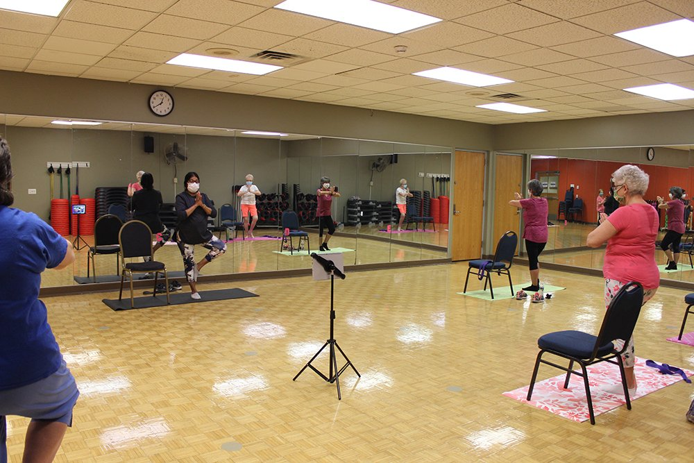 Senior members in a chair yoga group fitness class.